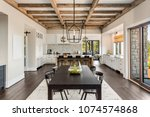 Stock photo stunning dining room and kitchen in new luxury home wood beams and elegant pendant lights accent 1074574868