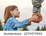 soldier holding hand of little... | Shutterstock . vector #1074575942