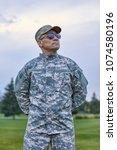 Small photo of Courageous brave soldier. Portrait of mature sergeant with spectacles and cap outdoor.
