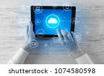 hand touching tablet with cloud ... | Shutterstock . vector #1074580598