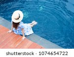woman is sitting at the pool...   Shutterstock . vector #1074654722