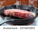 Small photo of Searing beef brisket steak on the electric stove with hot cast iron skillet