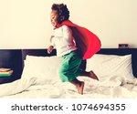 african descent kid jumping on... | Shutterstock . vector #1074694355