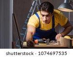 worker working in repair... | Shutterstock . vector #1074697535