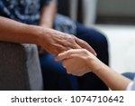 hand of elderly woman holding... | Shutterstock . vector #1074710642