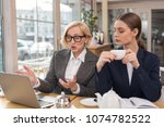 Small photo of Best partners. Concentrated young woman talking about business with her partner while having tea