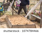 Small photo of photo of a fresh grave, which is ennobled by a graveyard worker