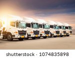 Small photo of New haulage truck fleet in container depot as transporatation, shipping and logistics business.