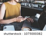 woman in city cafe  typing on... | Shutterstock . vector #1075000382