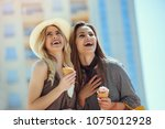 happy young women with shopping ... | Shutterstock . vector #1075012928
