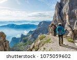 pair of mountaineers walking a... | Shutterstock . vector #1075059602