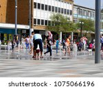 Small photo of Queens Square, Crawley, West Sussex, UK- April 21st, 2018: Random Children and Adults Enjoying the New Water Fountain and Seating Area, Inviting an Enjoyable Public Space for all.