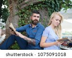 Small photo of Couple in love sit outdoor, nature background. Romantic date concept. Girl with pensive face fall in love with bearded man, couple reads poems. Romantic couple holds old books with poems.