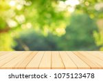 wood table top on blur green... | Shutterstock . vector #1075123478
