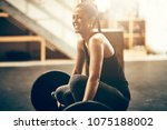 Small photo of Fit young woman in sportswear smiling while preparing for a workout session with heavy weights in a gym