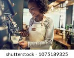 smiling young african barista... | Shutterstock . vector #1075189325