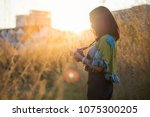 Photographer woman take photo with mirrorless camera.People side view,Asian traveler female sightseeing with  old camera against sunset background. Travel and Photographer concept.