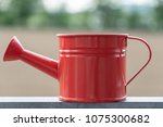 red watering can on unfocused... | Shutterstock . vector #1075300682