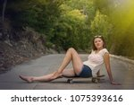 Small photo of Young woman sits on a skateboard on concrete road. Barefoot relaxed female in jeans shorts and white t-shirt sits with legs stretched out. Small bruise is visible on left leg. Active lifestyle concept