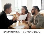Stock photo angry deceived couple customers disputing about mortgage loan or real estate problem with realtor 1075401572