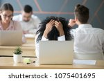 Small photo of Frustrated african woman feeling despair panic shock sitting in shared office with laptop holding head in hands, upset stressed black employee or student tired of work, worried about online problem