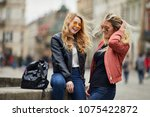 two girls sit on the fountain... | Shutterstock . vector #1075422872
