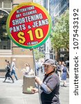 Small photo of Sydney, Australia - Nov 14, 2017: A man holding up a sign on Martin Place, drumming up business for a nearby fabric alteration store. He looks toward the camera. People walking around in the area.