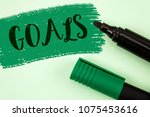 Small photo of Text sign showing Goals. Conceptual photo Desired Achievements Targets What you want to accomplish in the future written on Painted Green background Markers next to it.