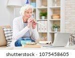 ecstatic senior woman in party... | Shutterstock . vector #1075458605