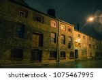 dark urban city alley at night... | Shutterstock . vector #1075467995