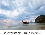 Small photo of Tropical sunset on Koh Mook island in Thailand. Landscape with longtail boat taken on Charlie beach, Haad Sai Yao - Haad Farang.