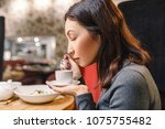 young eastern woman drinking... | Shutterstock . vector #1075755482