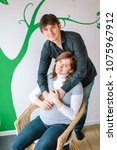 Small photo of love, healthcare, parentage concept. there is lovely couple, hansome man with funny eyes and his wife who is sitting in wicker chair, because of her pregnancy, he is hugging her
