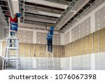 Construction worker installation ceiling - stock photo