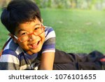 portrait of happy asian boy sit ... | Shutterstock . vector #1076101655