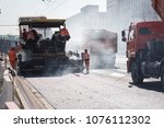 Small photo of heavy asphalt paver red truck and road vibrating roller seal ready for repair roads in a modern city