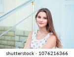 Teen girl with long brunette hair smiling sitting on steps. Beautiful young girl in white dress with brown polka dots. Mixed race asian russian. Horizontal image outdoors home office on background.