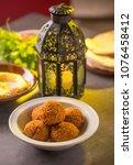 Small photo of Bowl of falafel, hummus and salad arranged along with Ramadan traditional lamp.