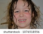 Small photo of child with long, wet, unresolved hair