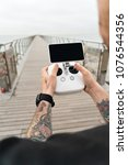 Small photo of Young professional or amateur photographer or drone pilot holds remote control panel with screen and controls ready to fly quadrocopter in air to see birds point of view.Hipster user of new technology