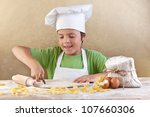 Little chef cutting the dough making pasta the traditional way - stock photo