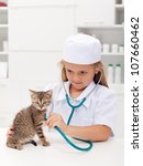 Little girl playing at the veterinary - consulting her little kitten - stock photo