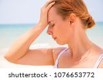 Small photo of Headache woman on sunny beach. Woman with sunstroke. Hot sun danger. Health problem on holiday. Medicine on vacation. Dangerous sun. Beach life. Sunstroke on sunny beach. Healthcare in tropics