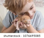 Stock photo happy caucasian boy hold in his palm little newborn kitten 1076695085