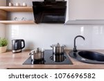 Stock photo contemporary kitchen with exhaust hood new design black sink and induction hob 1076696582