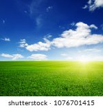green field  blue sky and sun.  | Shutterstock . vector #1076701415