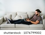 white man using laptop on sofa | Shutterstock . vector #1076799002