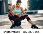 fit young woman sitting on... | Shutterstock . vector #1076873156