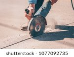 the worker saws the asphalt... | Shutterstock . vector #1077092735