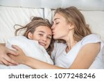 mom kissing happy daughter on... | Shutterstock . vector #1077248246